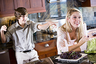 Teenage girl daydreaming in kitchen brother poking