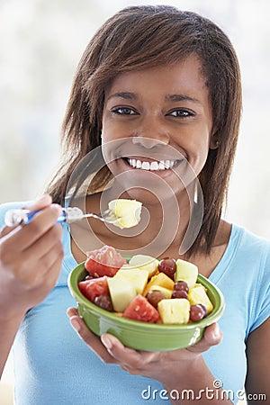 Teenage Girl Eating Fresh Fruit Salad