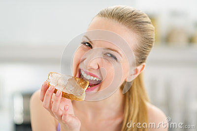 Teenage girl eating toast with chocolate cream