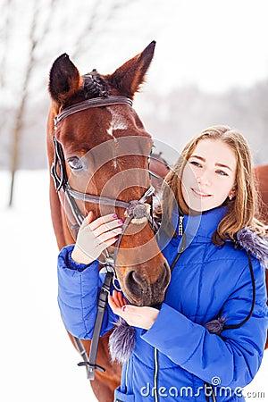 Free Teenage Girl Feeding Bay Horse On Winter Field Royalty Free Stock Photos - 87687948
