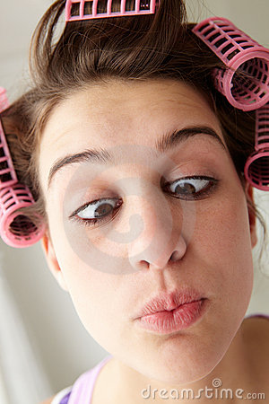 Teenage girl with hair in curlers pulling a face