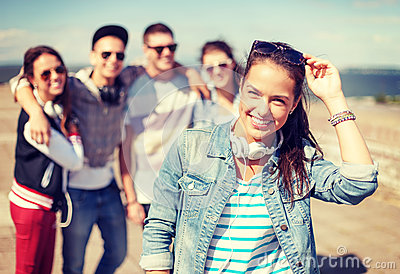 Teenage girl with headphones and friends outside