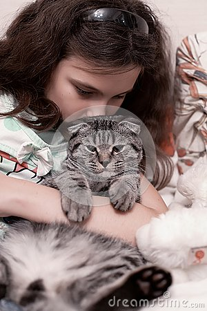 Teenage girl holding kitten