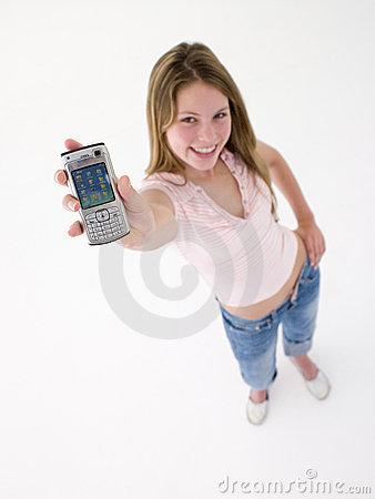 Teenage girl holding up cellular phone and smiling