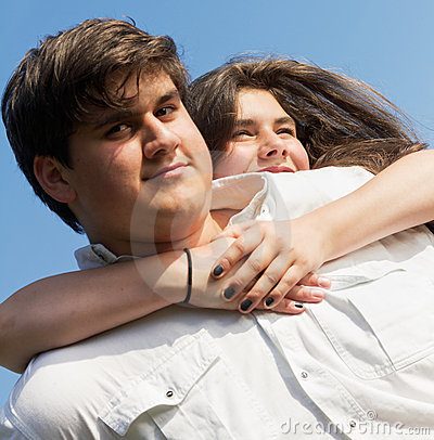 Teenage girl hugging boy