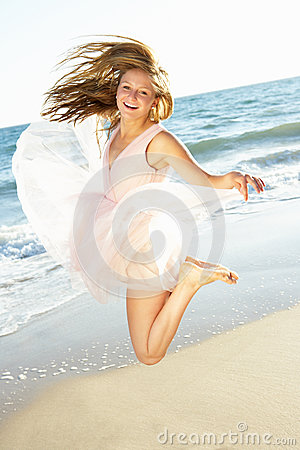 Teenage Girl Jumping In Air On Beach Holiday