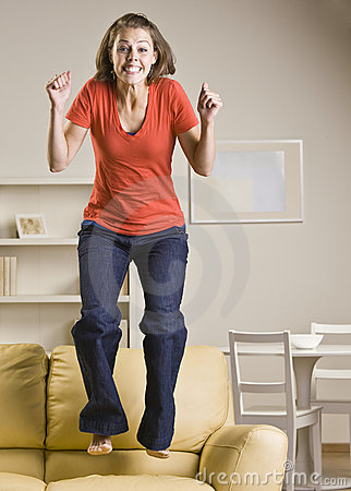Teenage girl jumping on sofa