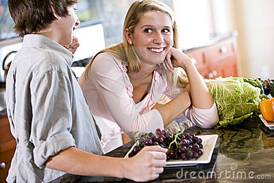 Teenage girl on kitchen counter with brother
