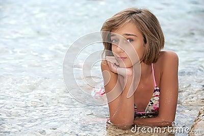 Teenage girl laying in the sea wate