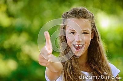 Teenage girl lifts thumb upwards