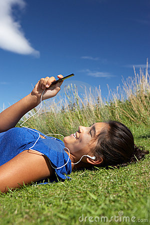 Teenage girl lying on grass with mp3 player