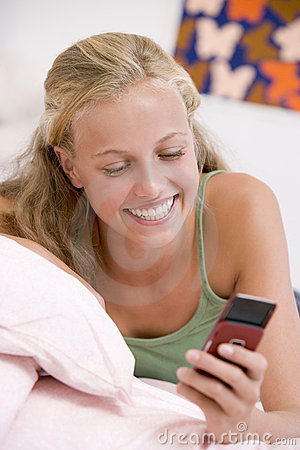 Teenage Girl Lying On Her Bed Using Mobile Phone