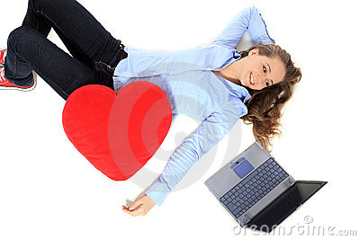 Teenage girl lying next to her laptop