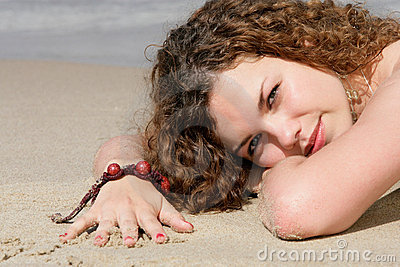 Teenage girl lying on sand