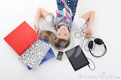 Teenage girl lying with tablet pc, phone and headphones