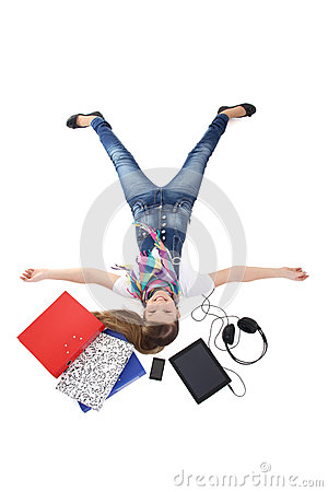 Teenage girl lying with tablet pc, phone and headphones over whi