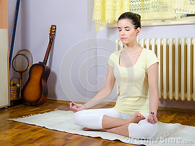 teenage girl meditating in yoga pose in her room stock