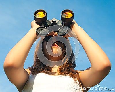 Teenage girl observing with binoculars