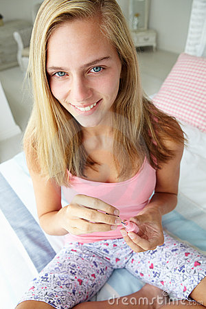 Teenage girl painting nails on bed