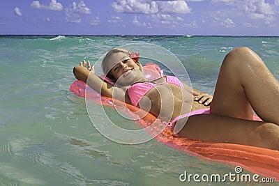 Teenage girl in pink bikini floating