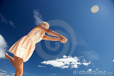 Teenage girl playing beach volleyball