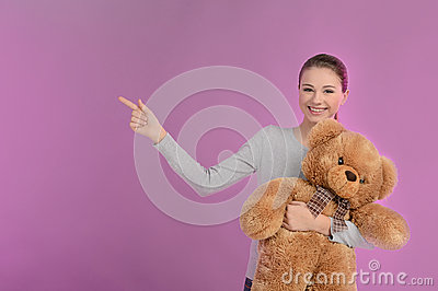 Teenage girl pointing. Happy teenage girl holding a teddy bear a