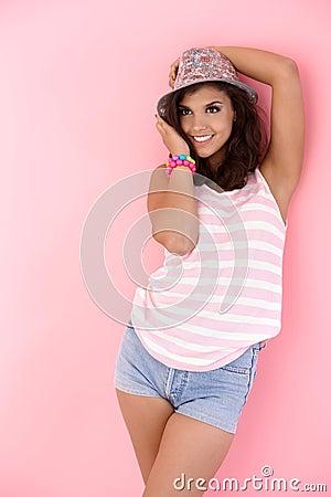 Teenage girl posing over pink background