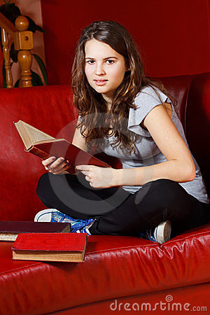 Teenage girl reading at home