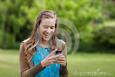Teenage girl receiving a text on her mobile phone