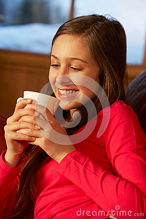 Teenage Girl Relaxing On Sofa With Hot Drink