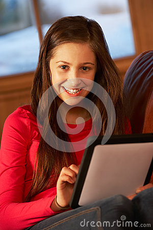 Teenage Girl Relaxing On Sofa With Tablet Computer