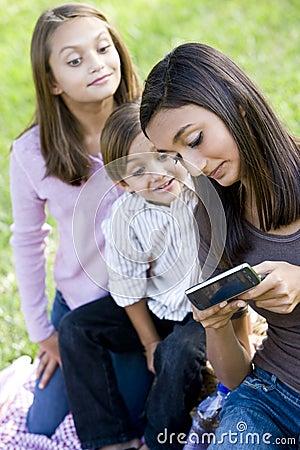 Teenage girl showing mobile phone to siblings