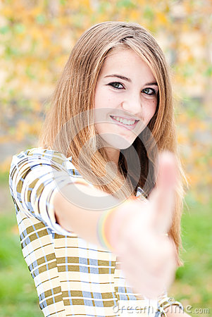 Teenage girl showing thumb up on autumn day