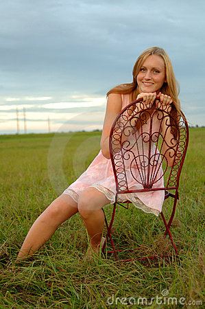 Teenage girl sitting in field on chair