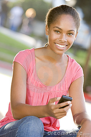 Teenage Girl Sitting Outdoors Using Mobile Phone