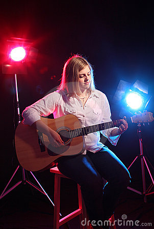 Teenage girl sitting on stage with a guitar