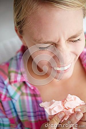Teenage girl sneezing into tissue