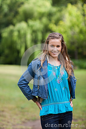 Teenage girl standing upright in the countryside