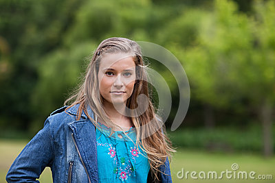 Teenage girl standing upright in a park