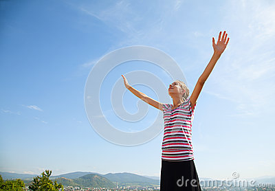 Teenage girl staying with raised hands