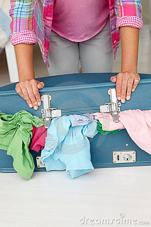 Teenage girl struggling to close full suitcase