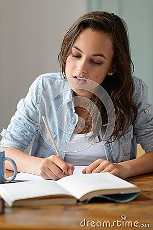 Teenage girl studying book writing notes