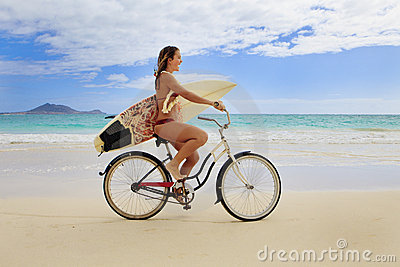 Teenage girl with surfboard and bike
