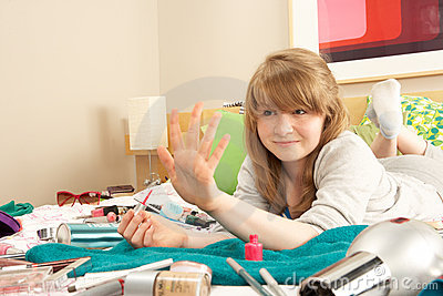 Teenage Girl In Untidy Bedroom Painting Nails