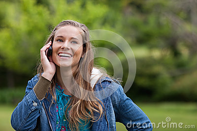 Teenage girl using her mobile phone while smiling