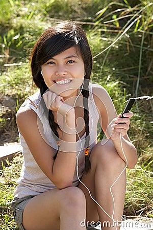 Teenage girl using mp3 player outdoors