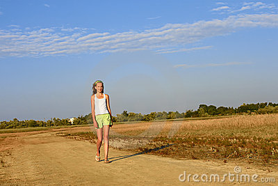 Teenage girl walking on the sandy road