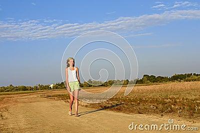 Teenage girl walking on the sandy road
