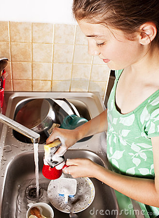 Teenage Girl Washing Dishes In Her Kitchen Royalty Free