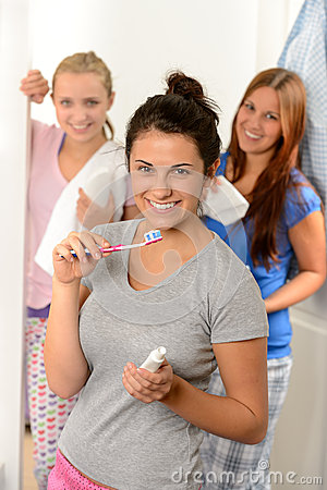 Teenage girl washing her teeth with friends